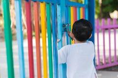 在设法的栅格后的哀伤的亚洲孩子逃脱 浅DOF 免版税图库摄影