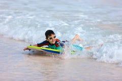 在识别不明飞机委员会的男孩游泳 免版税图库摄影