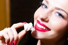 在诱人的迷人的美丽的少妇的特写镜头画象有蓝眼睛、红色嘴唇&手的有拿着糖果的红色钉子的 免版税库存图片