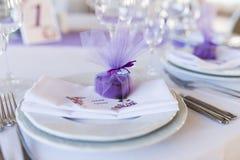 在说谎在一块白色板材的心脏形状的一婚礼紫色bonbonniere 免版税库存照片