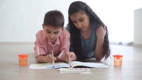 在说谎在地板上的册页的愉快的弟弟和姐妹油漆 股票录像