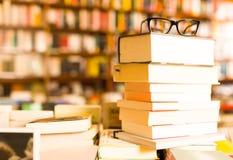 在说谎在桌上的堆的玻璃书顶部在书店 免版税库存图片