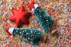 在说谎在泡沫球的圣诞老人帽子的圣诞树,红色圣诞节星 免版税库存图片