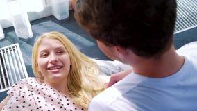 在说谎在膝部的快乐的白肤金发的妇女肩膀射击她人微笑 股票视频