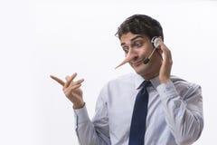 在说谎对他的对手的电话的商人 库存照片