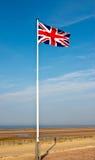 在诺曼底海滩的英国国旗 图库摄影