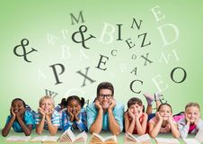 在读与老师的多文化孩子附近的许多信件 免版税库存图片