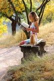 在读取妇女年轻人附近的书猫 库存照片