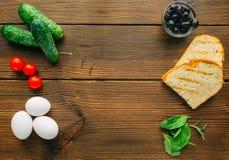 在调味料、橄榄、草本和鸡蛋的生肉 免版税图库摄影