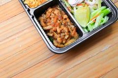 在调味汁甜点的猪肉与柠檬片,在箱子黑色泰国样式食物的菜没有木桌背景 免版税库存照片