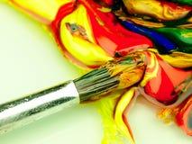 在调色板混合的色的油漆 在前景的肮脏的刷子 免版税库存图片