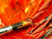 在调色板混合的色的油漆 在前景的肮脏的刷子 免版税库存照片