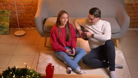 在谈下年轻白种人朋友看法的特写镜头上面坐地毯用酒在舒适家庭圣诞节气氛 股票录像