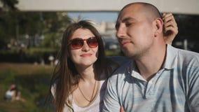 在谈话的爱的愉快的年轻夫妇,当坐公园长椅时 股票录像