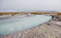 在谷中的白色宽迅速河在岩石小山背景  库存照片