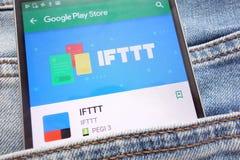 在谷歌戏剧在智能手机显示的商店网站上的IFTTT应用程序掩藏在牛仔裤装在口袋里 免版税库存照片