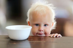 在谷物碗旁边的逗人喜爱的矮小的一个岁女婴在Kitche 免版税库存照片