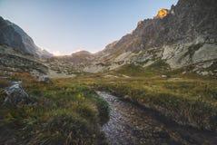在谷的小河在日落的山峰下 免版税图库摄影
