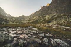 在谷的小河在日落的山峰下 免版税库存图片