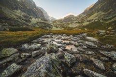 在谷的小河在日落的山峰下 库存照片