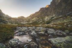 在谷的小河在日落的山峰下 免版税库存照片
