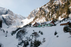 在谷的瑞士山中的牧人小屋,围拢由山 免版税库存照片