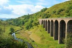 在谷的高架桥在河旁边 免版税图库摄影