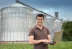 在谷粮仓前面的农夫 免版税图库摄影