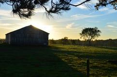 在谷仓后的日出农场的 库存图片