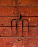 在谷仓墙壁上的生锈的干草叉子 免版税库存图片