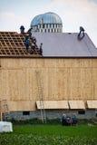 在谷仓屋顶的安曼人工作 库存照片
