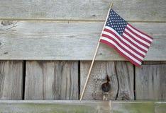 在谷仓木房屋板壁的美国国旗 库存照片