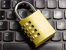 在象征数据保密的膝上型计算机键盘的闭合的组合挂锁 免版税库存图片