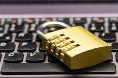 在象征数据保密的膝上型计算机键盘的闭合的组合挂锁 图库摄影