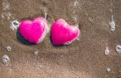 在象征爱的海滩的两红色心脏 免版税库存图片