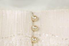 在象牙婚礼礼服的珍珠按钮 免版税库存图片