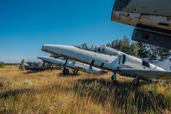 在象草的地面的被放弃的打破的老军用战斗机飞机 库存照片