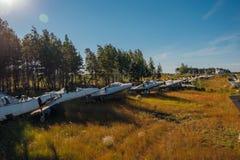 在象草的地面的被放弃的打破的老军用战斗机飞机 免版税库存图片