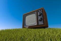 在象草的小山的老古色古香的木电视 图库摄影