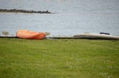 在象草的码头的橙色皮船 图库摄影