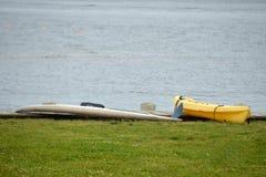 在象草的码头的黄色皮船 库存图片