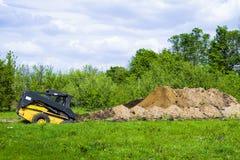 在象草的领域的挖掘机开掘的坑与背景的庭院 免版税库存照片