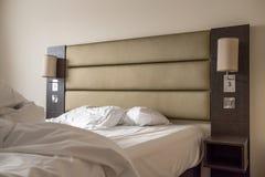 在豪华公寓看见的没有整理好的特大双人床 图库摄影
