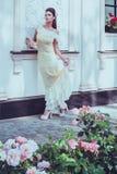 在豪华大厦门面附近的美丽的妇女 免版税库存照片