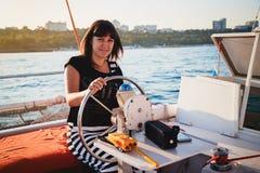在豪华小船的年轻俏丽的微笑的妇女航行在海,温暖的夏天晚上 图库摄影