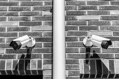 在豪华居民住房砖墙上的两台cctv监视保安系统照相机公开和私有安全黑色的 图库摄影