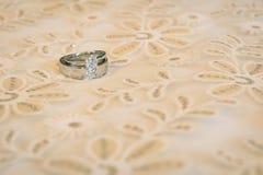 在豪华床上的婚戒 库存图片