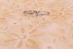 在豪华床上的婚戒 免版税库存照片
