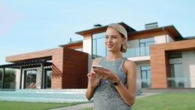 在豪华房子外部附近的美女键入的机动性 成功的生活方式 股票录像