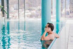 在豪华旅馆供以人员谈话在游泳池里面的手机 库存照片